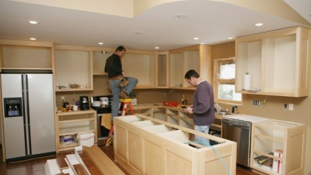 Two men installing cabinets into a kitchen